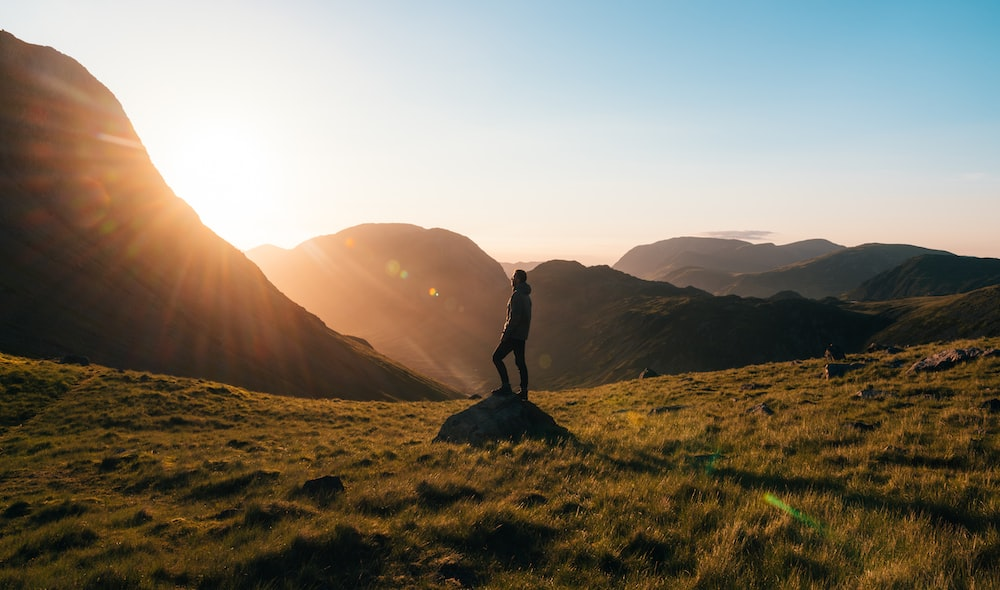 man standing on top of rock in an open field at golden hour