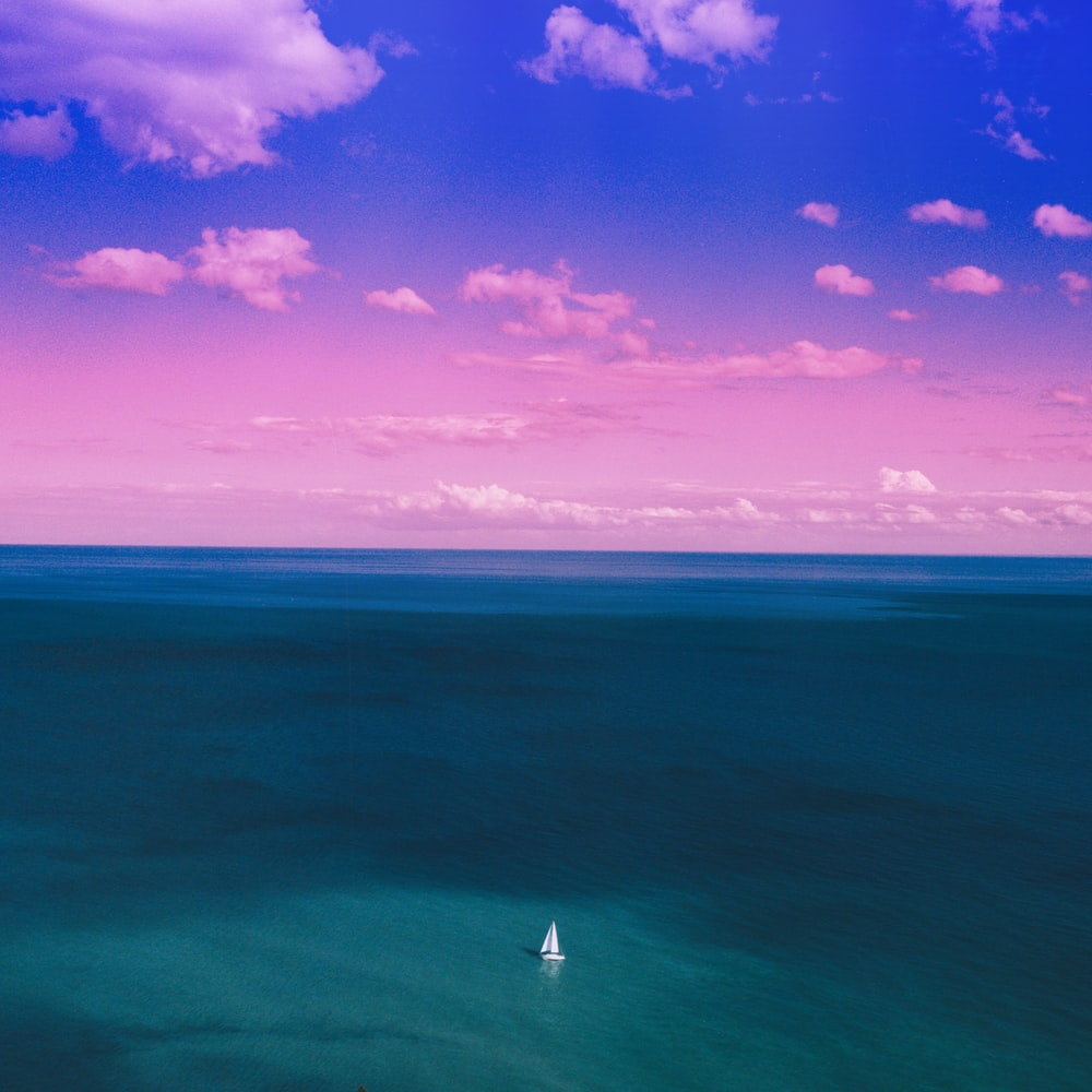 sailboat on blue ocean under purple and blue sky