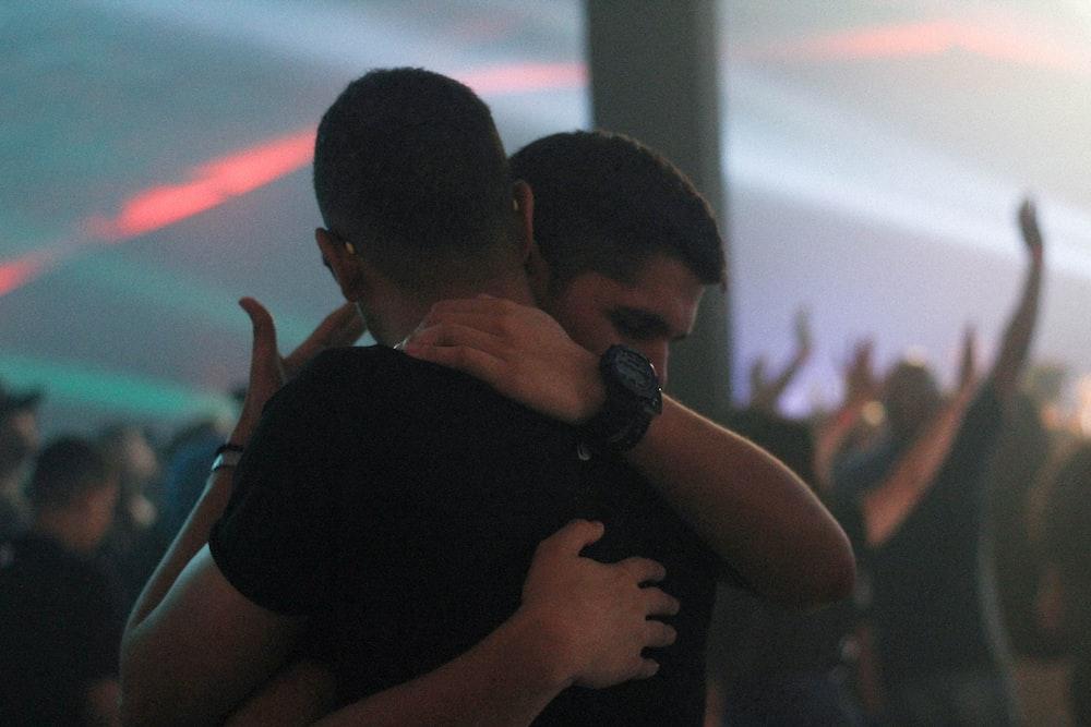 two men hugging each other inside bar