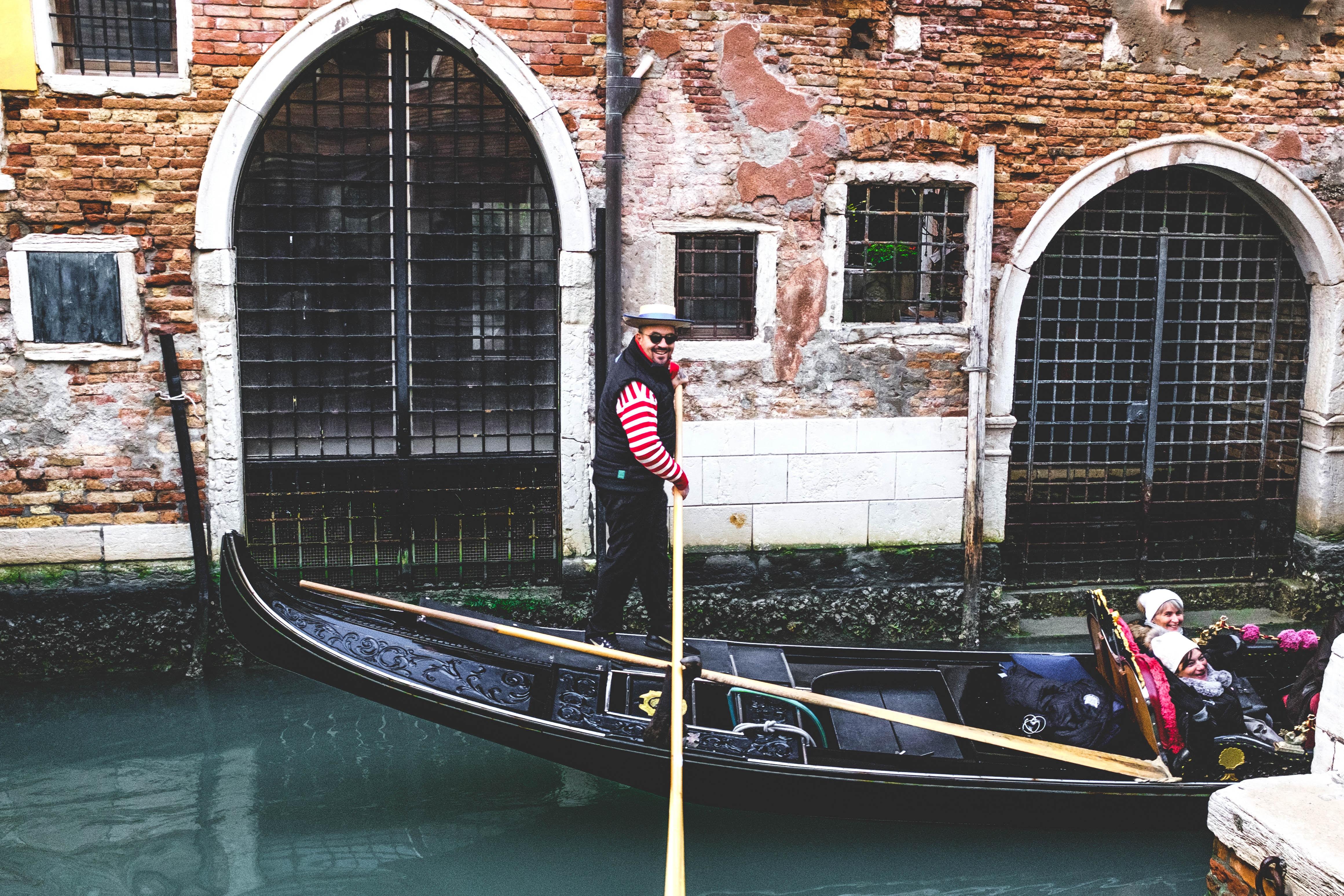 man riding on black boat during daytime