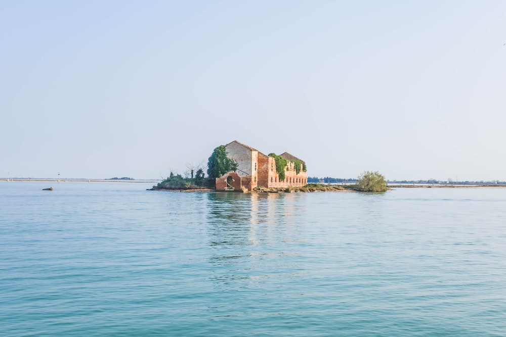 beige and red concrete house surrounded by body of water