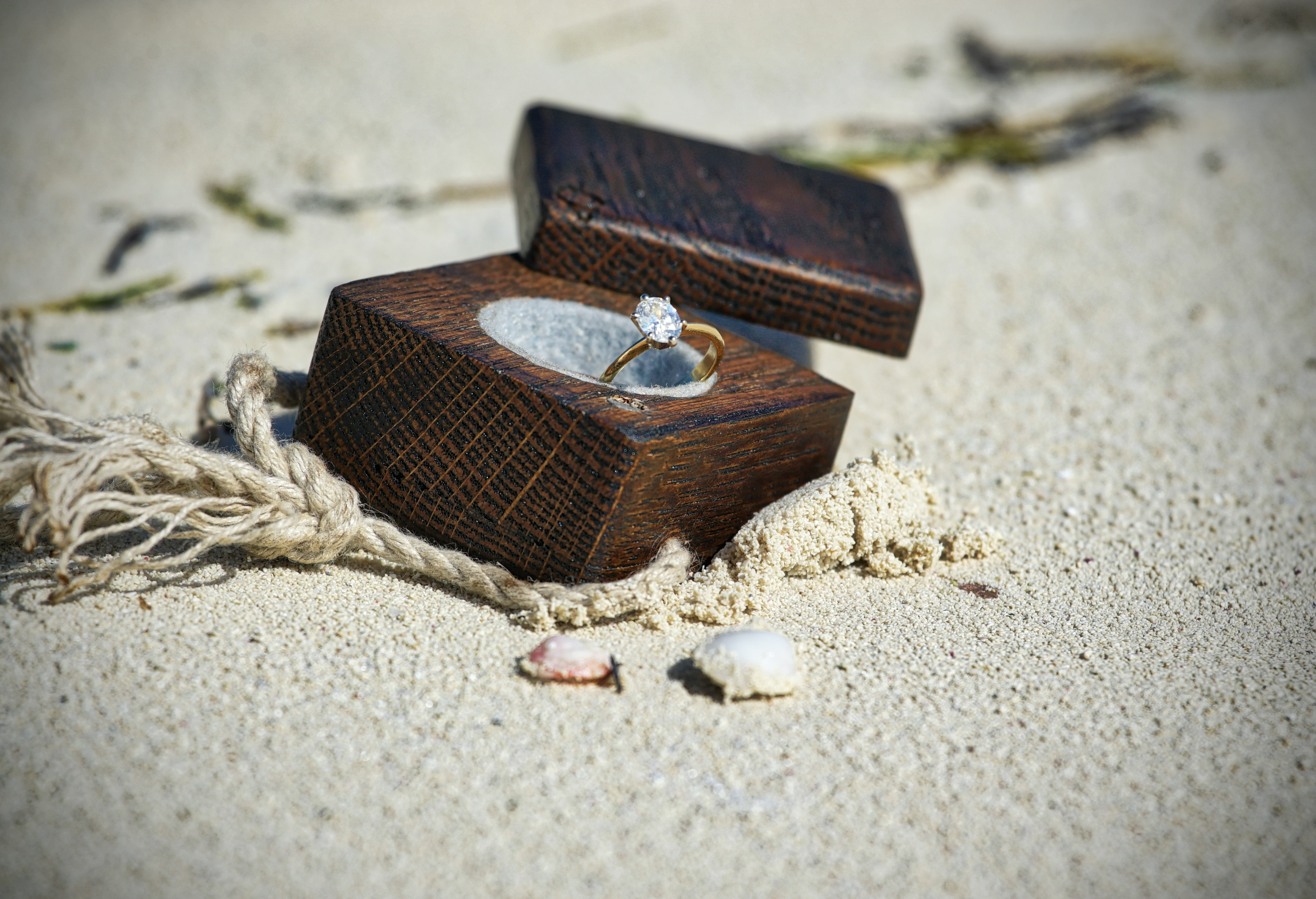 gold-colored clear gemstone ring in brown wooden box on sand