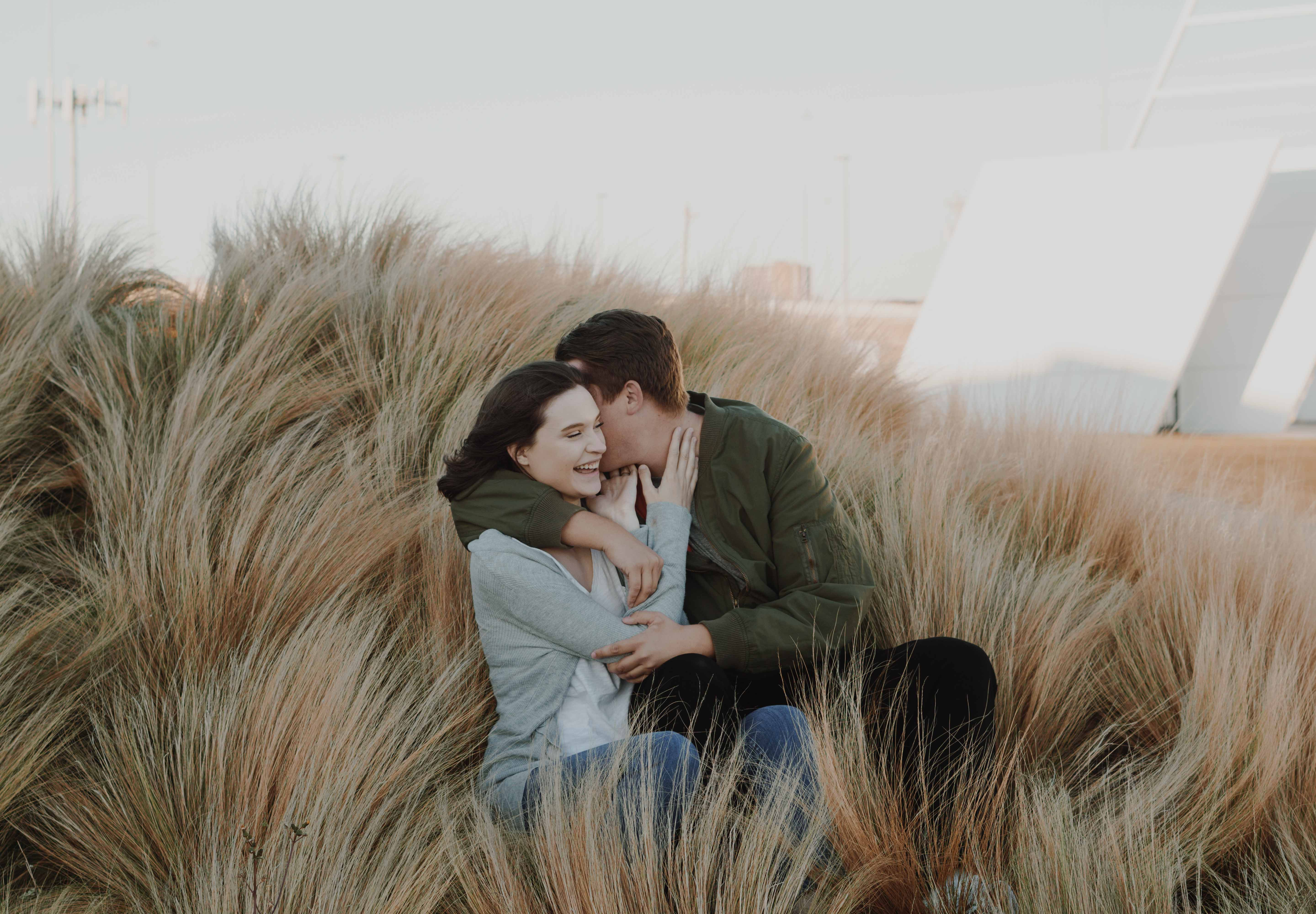 man whispering on womans ear on brown grass field