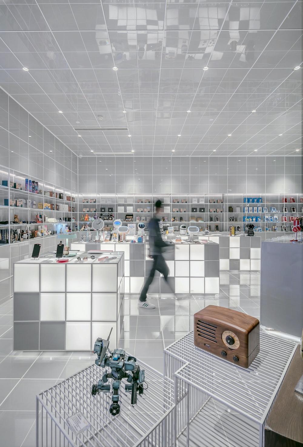 man walking beside white cube decoration