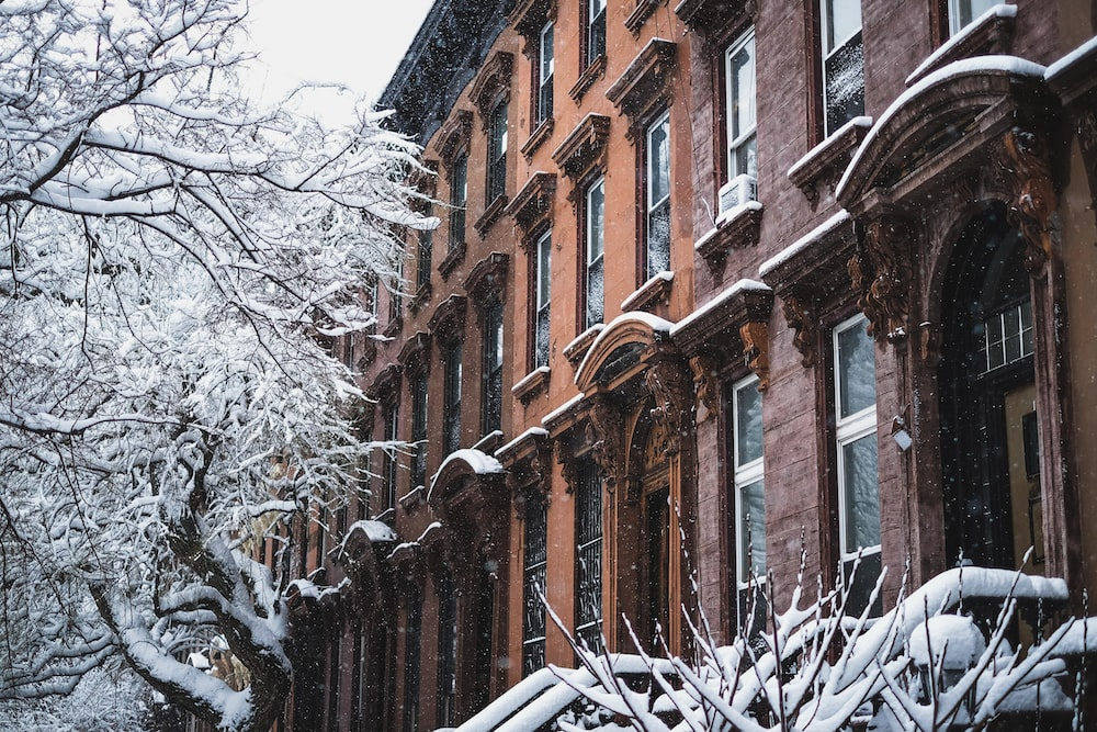 brown building near bare trees covered with snow