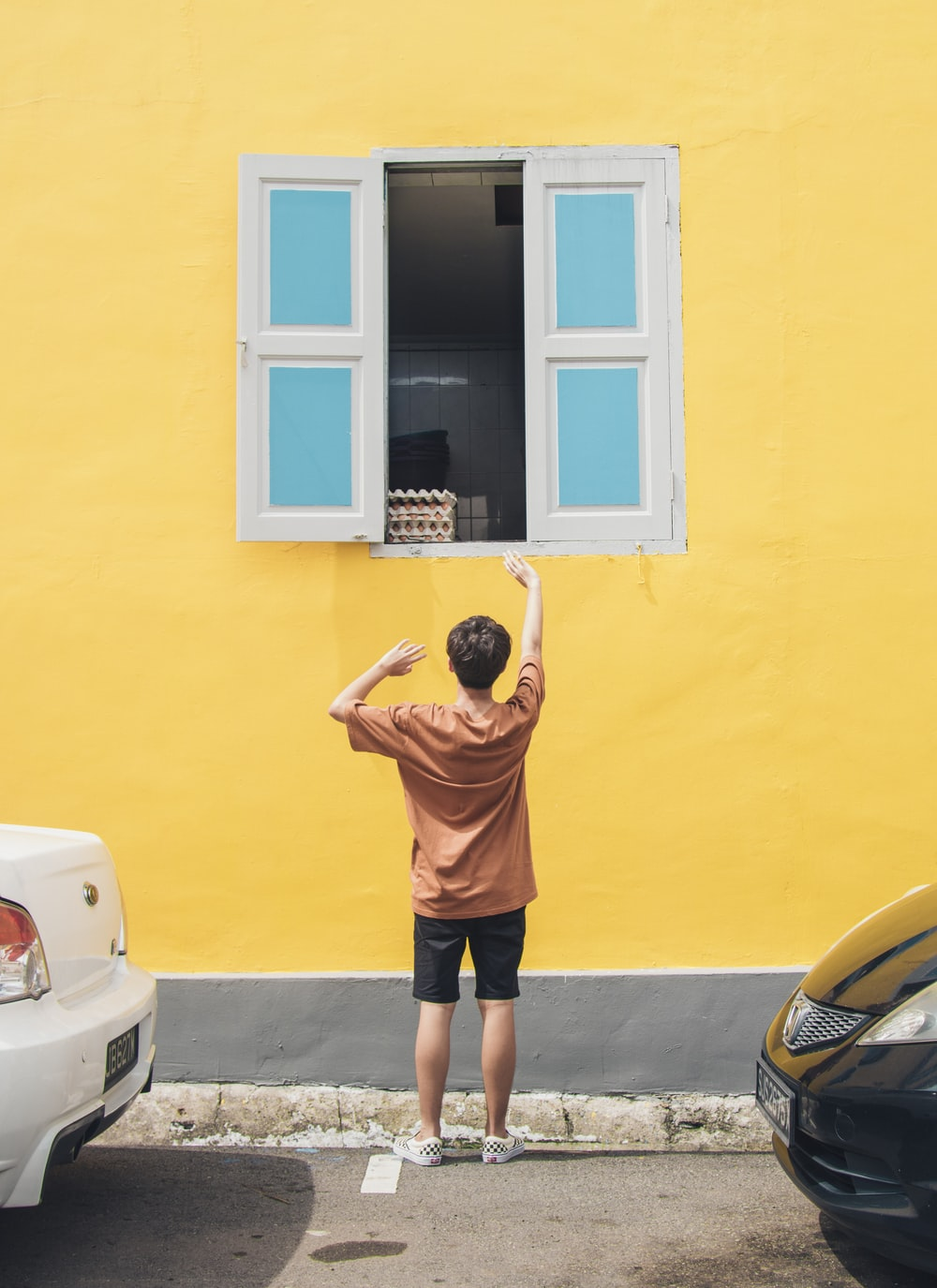 boy in front of window raising hand during daytime