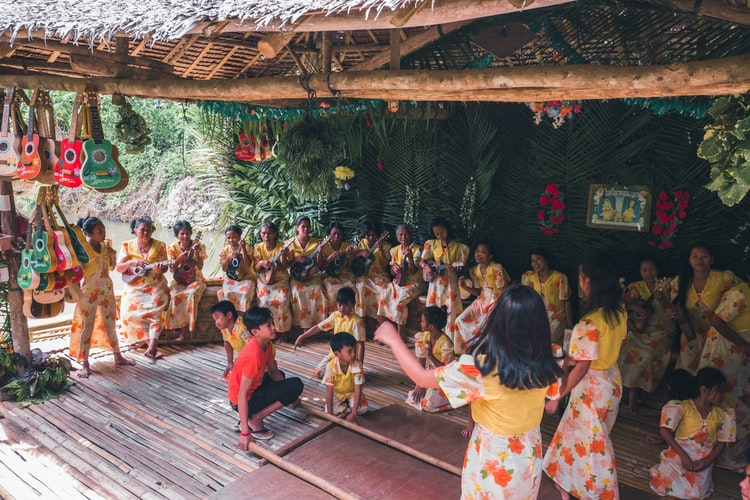A group of children in colorful clothing playing music and dancing.