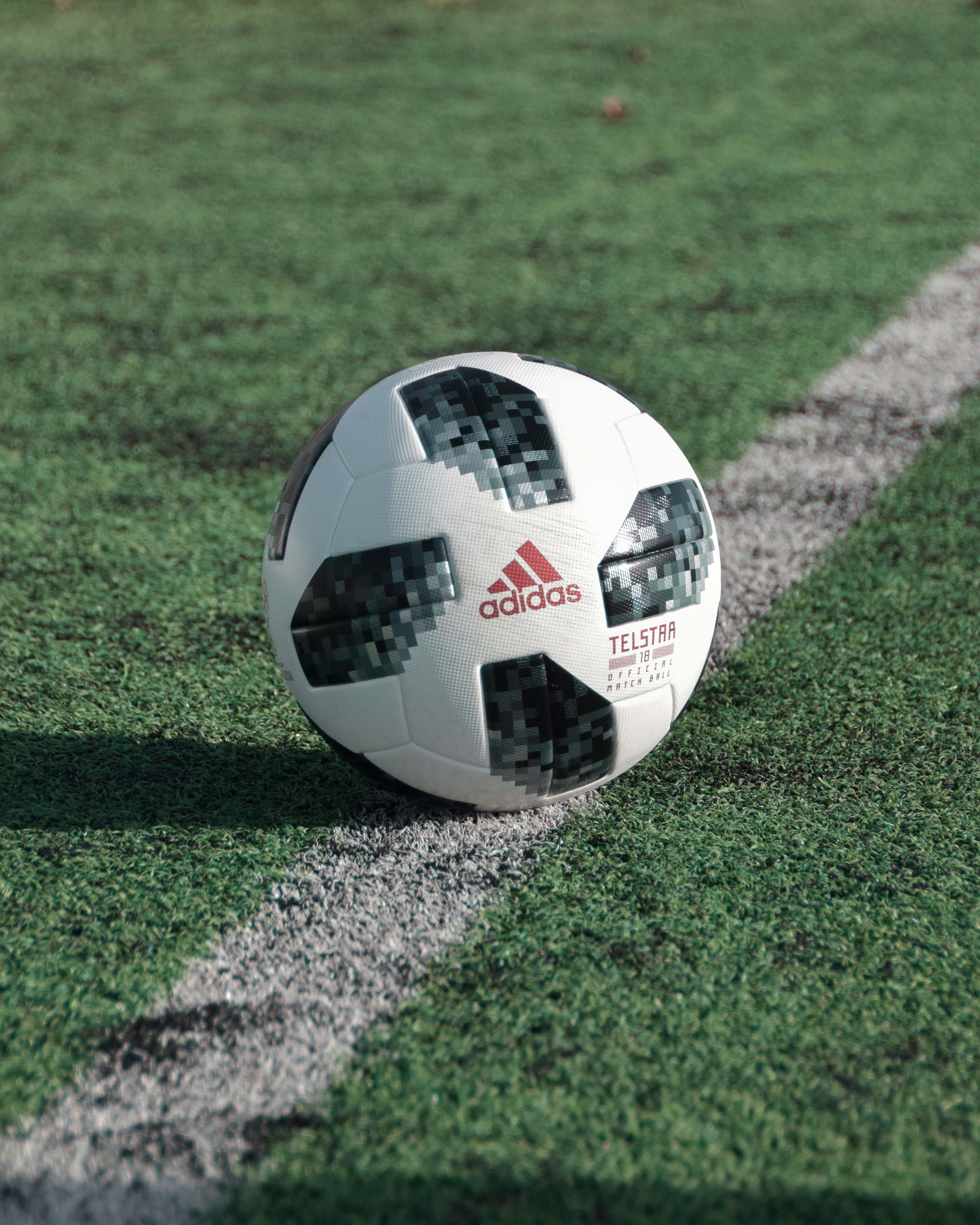 close-up photography of adidas soccer ball on field
