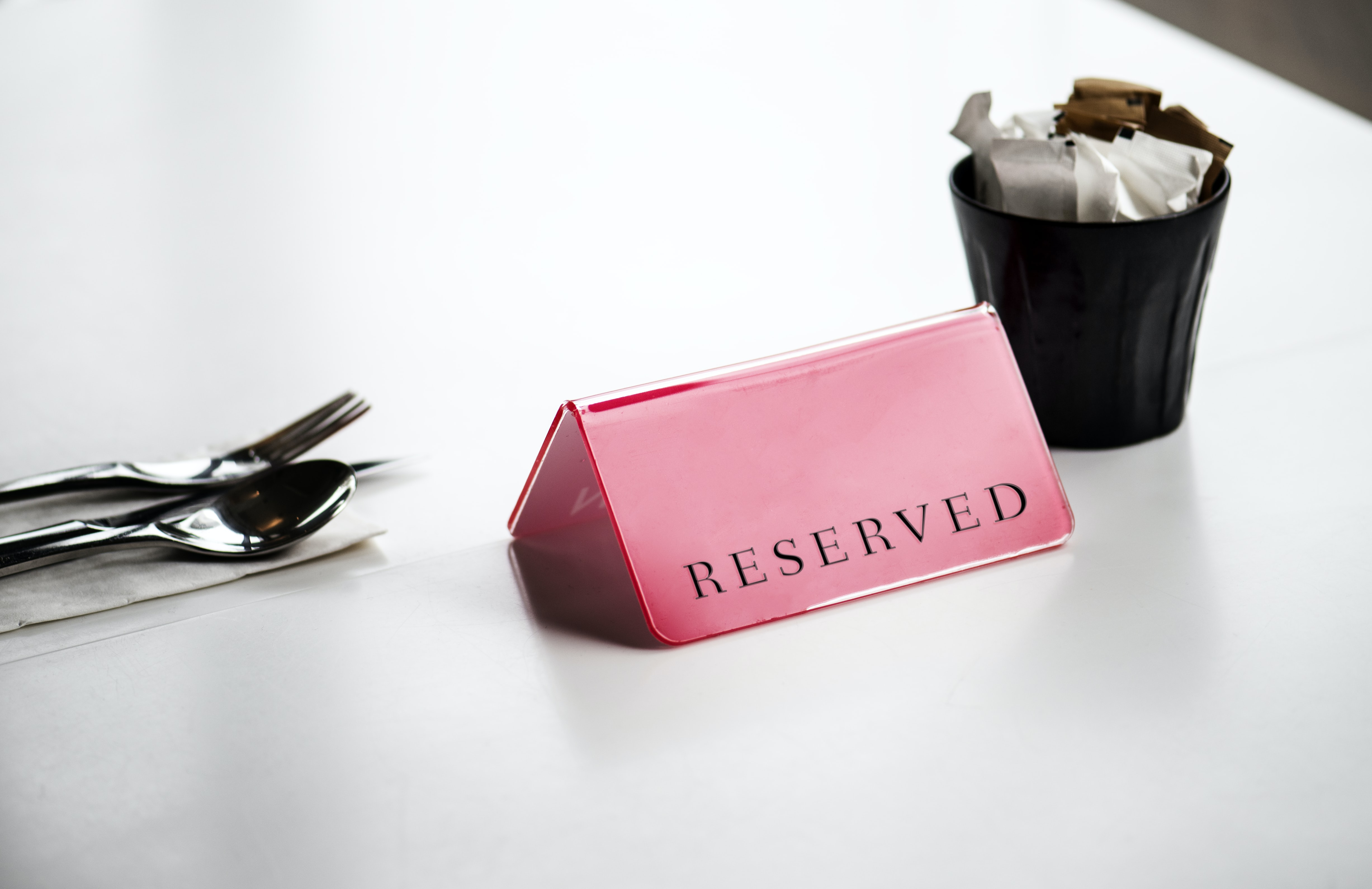 pink reserved signage near black cuo and gray stainless steel spoon and fork