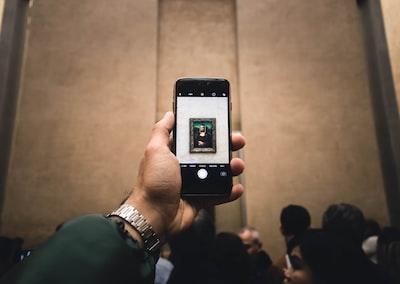 person holding black android smartphone da vinci zoom background