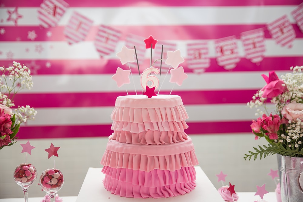 pink birthday cake on tabletop