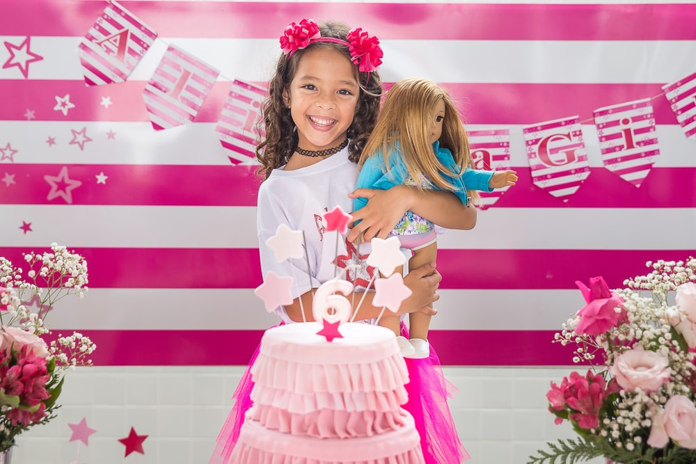 girl happily smiling holding doll with pink cake in front of her