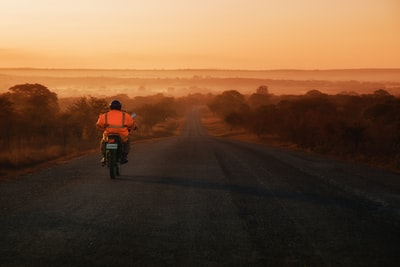 man riding on motorcycle between trees zambia zoom background