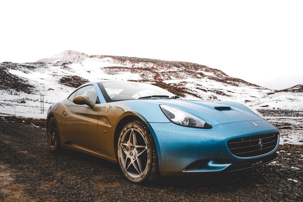 blue sports car parked near hill