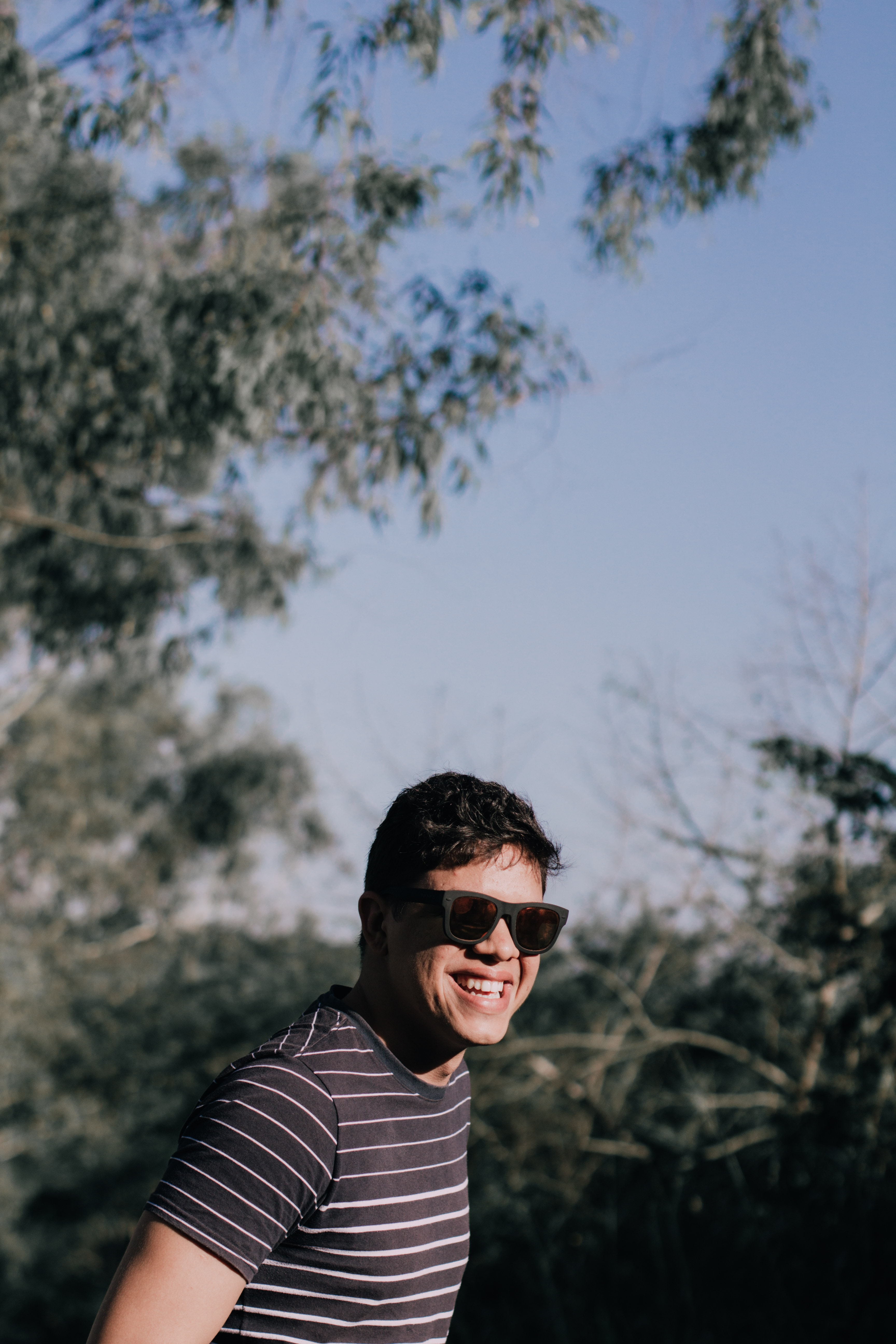 selective focus photography of man smiling while standing near trees