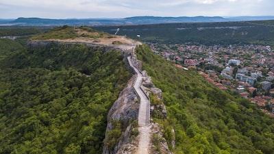 brown wooden bridge on mountain peak near cityscape bulgaria teams background