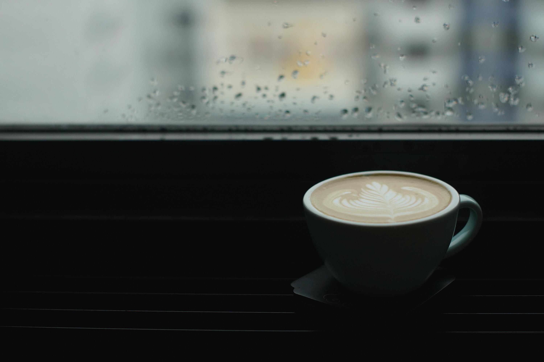 blue ceramic teacup beside window pane