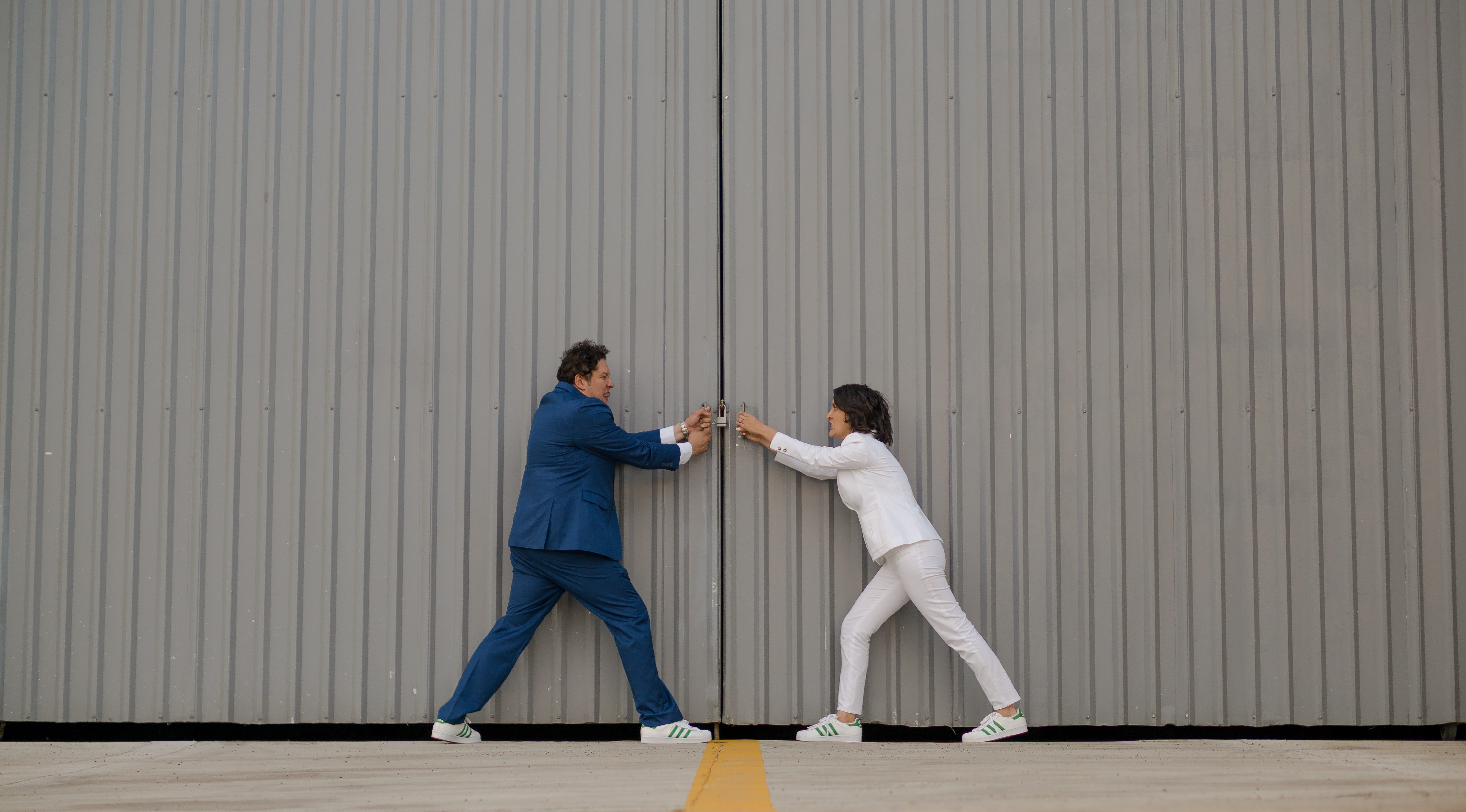 man and woman standing beside gray wall