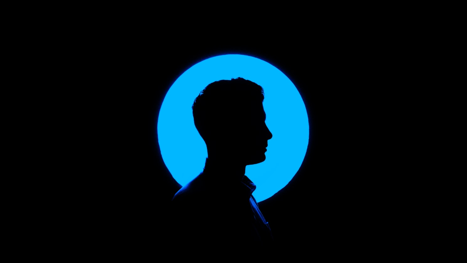 Silhouette of a man in front of a blue circle