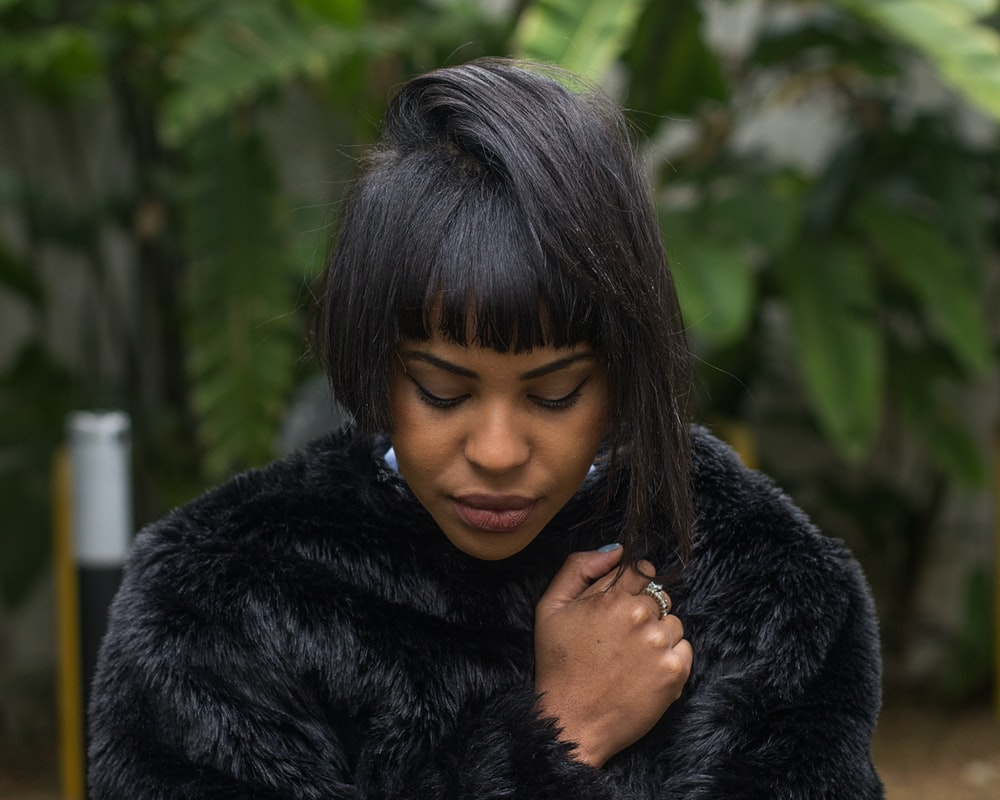 woman wearing black coat standing beside tree