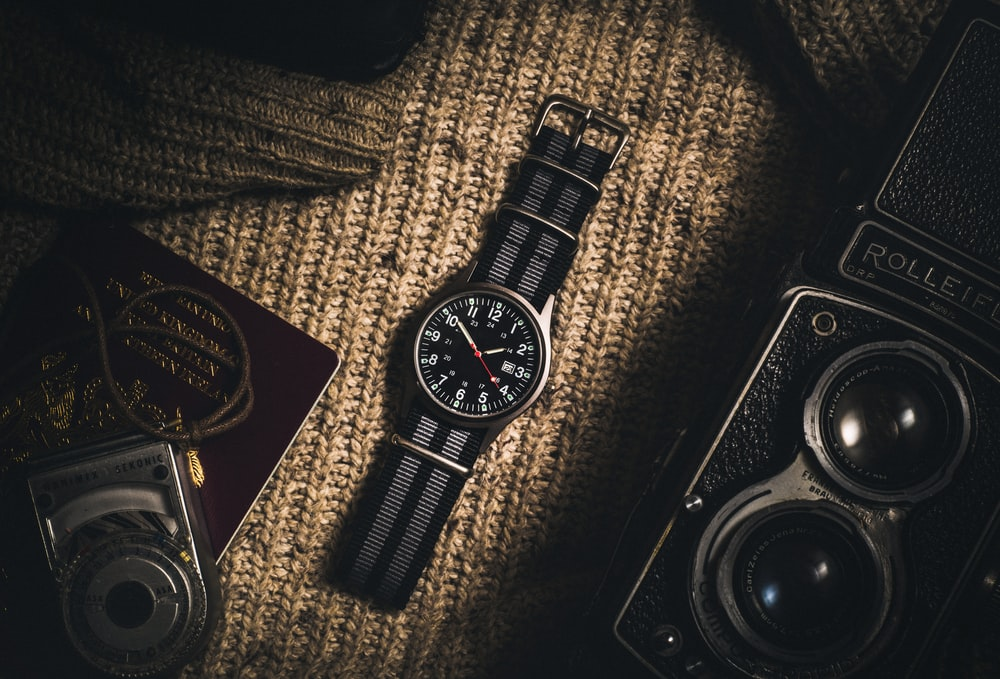 analog watch on brown textile