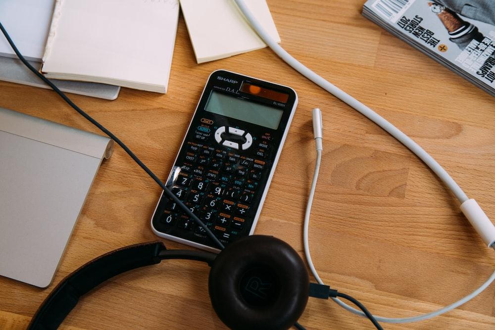 black scientific calculator beside black headphones
