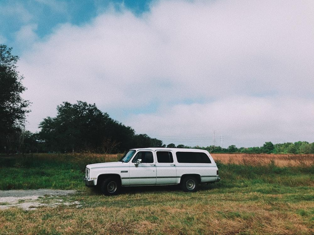 white station wagon on grass field