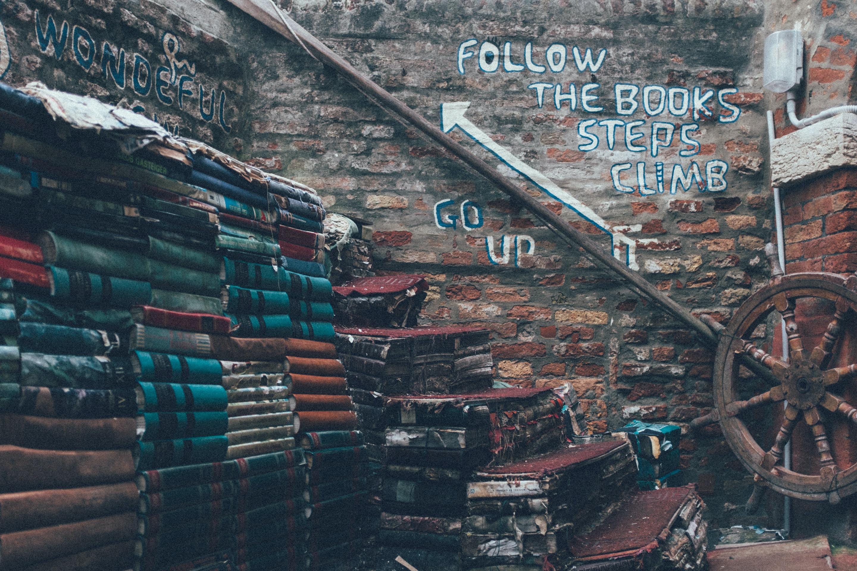pile of books beside ship's wheel