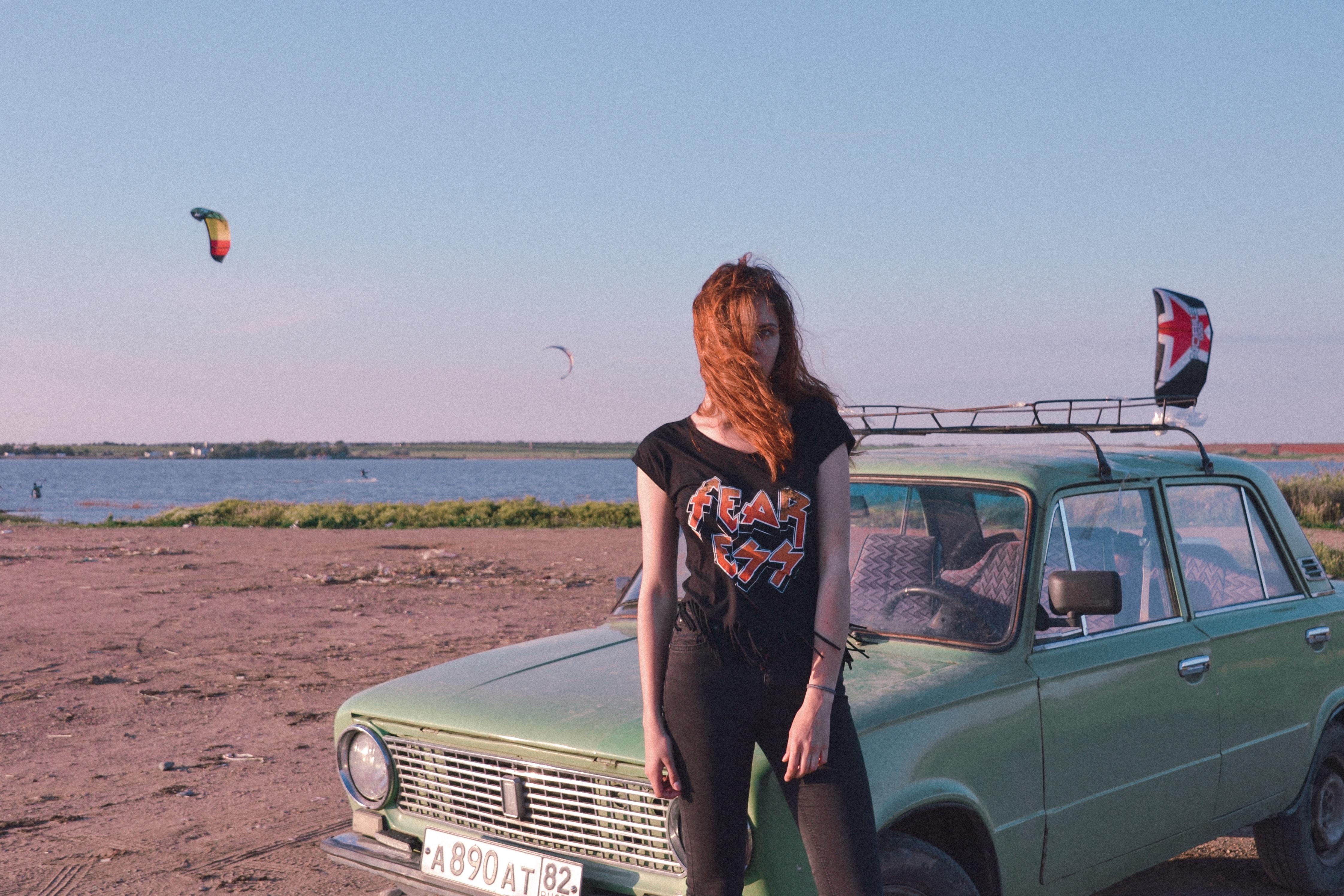 woman standing near blue car on seashore