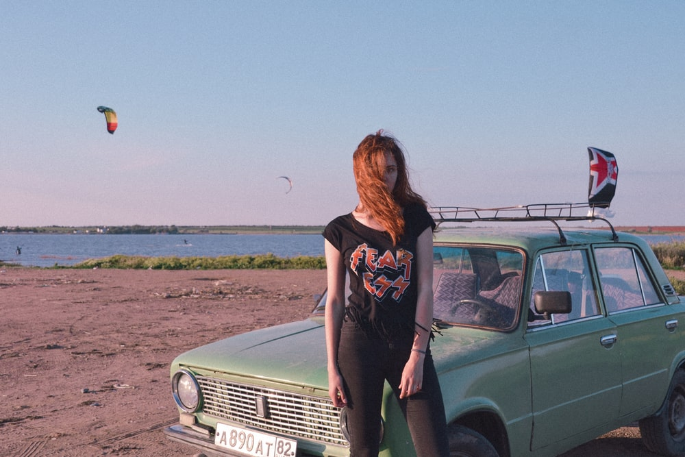 woman standing near blue car on seashore
