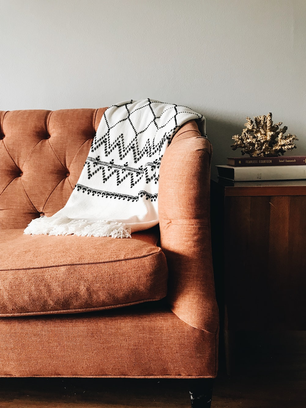 white and black textile on brown couch