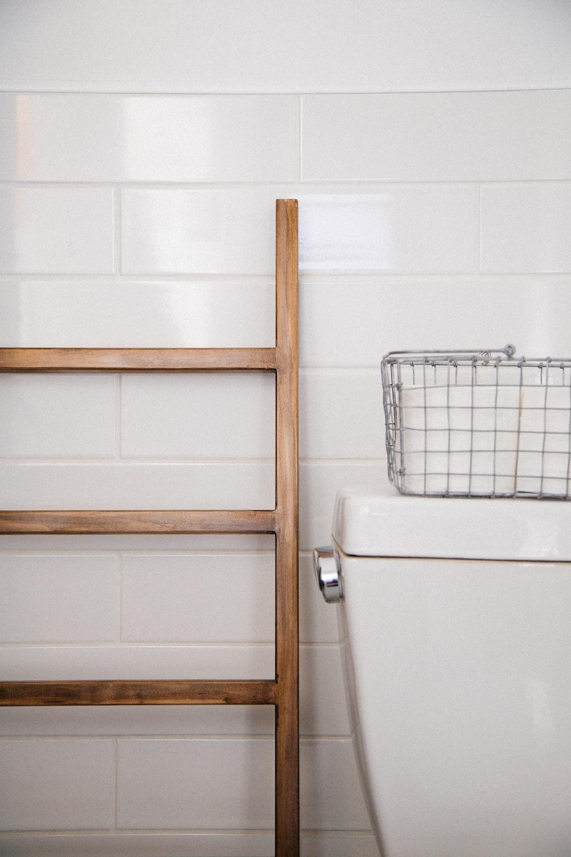 stainless steel basket on top white ceramic toilet bowl
