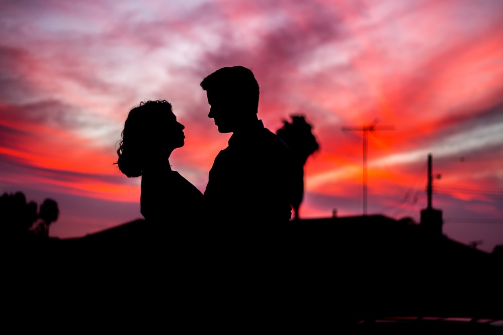 silhouette of man and woman facing each other during golden hour