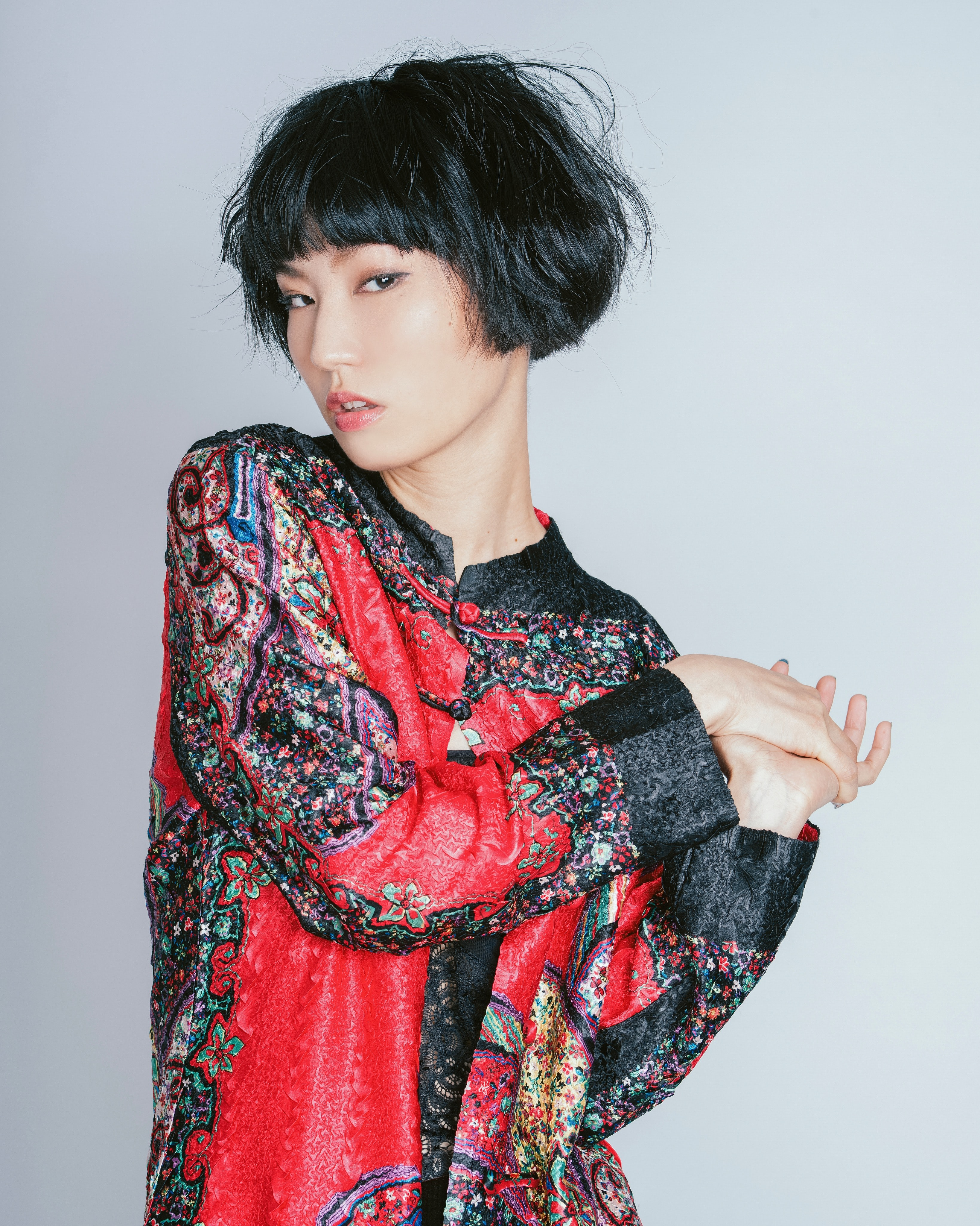 woman wearing floral long-sleeved shirt holding her hand