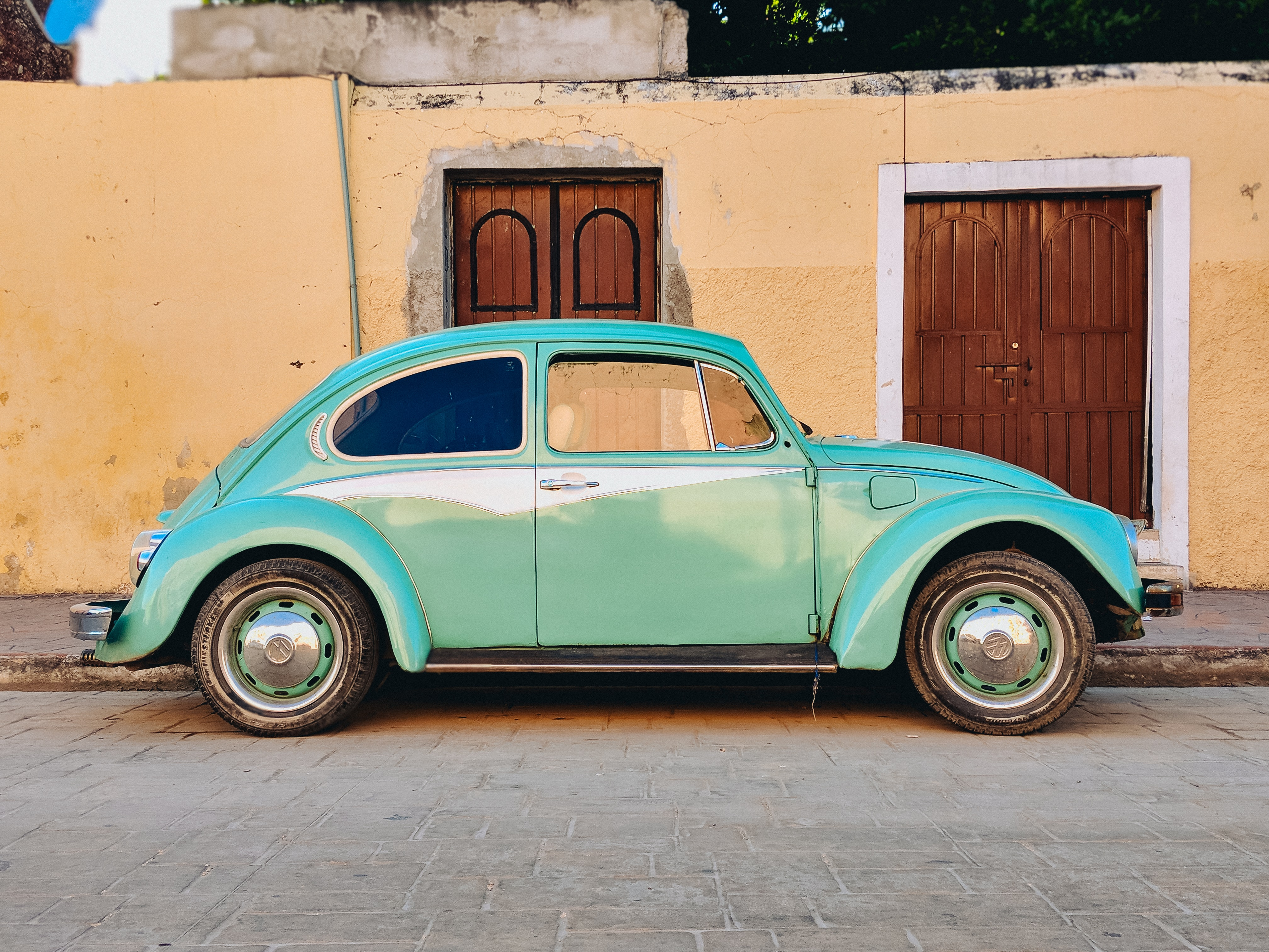 teal Volkswagen Beetle parked near brown house