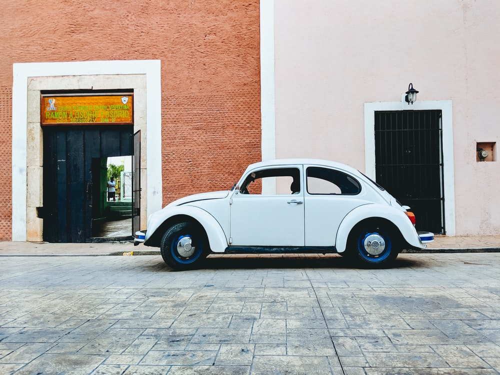 white Volkswagen beetle parked near building during daytime