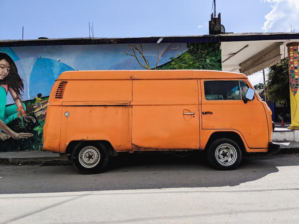orange van parked beside house