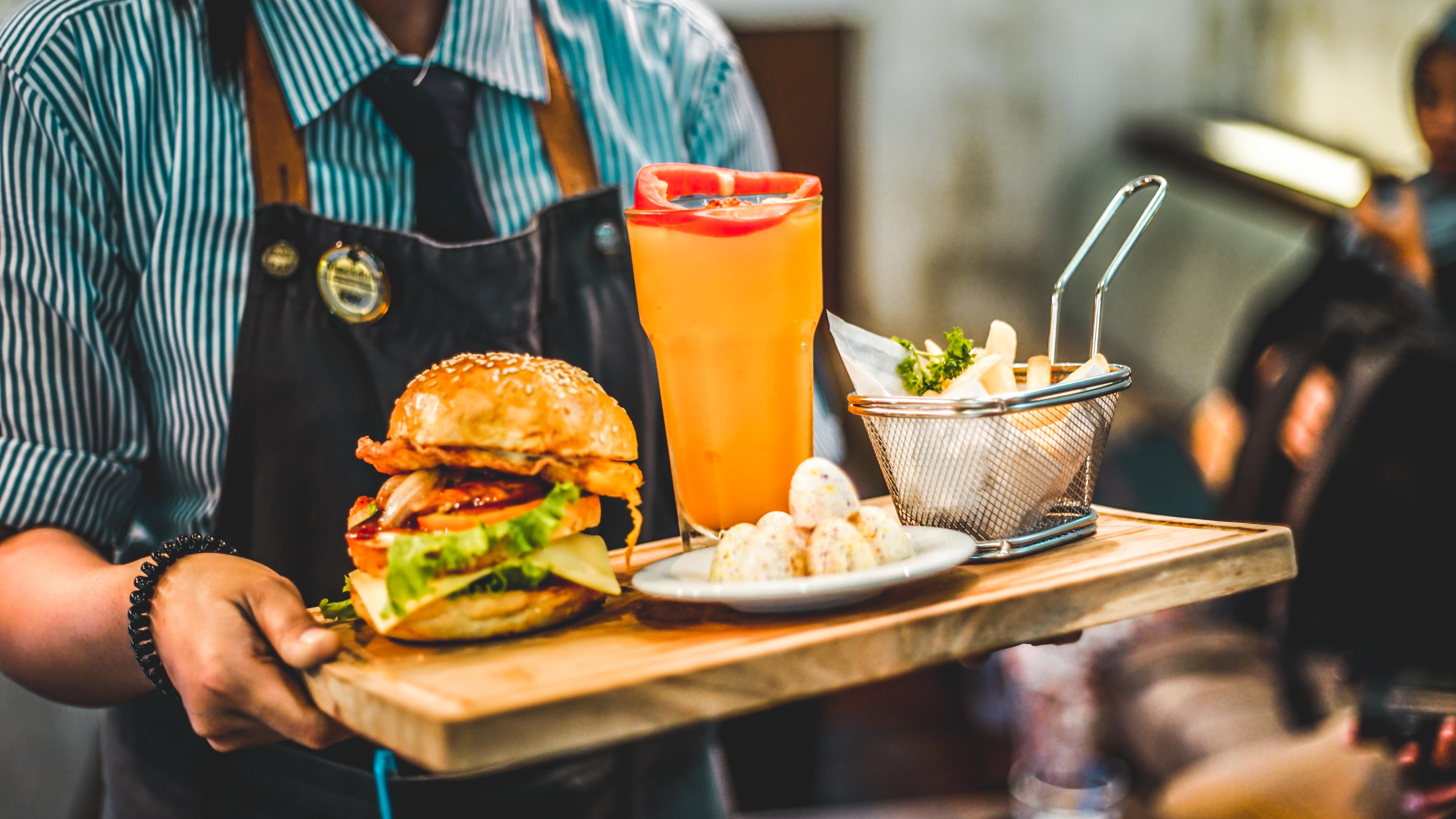 person serving burger with pitcher of juice