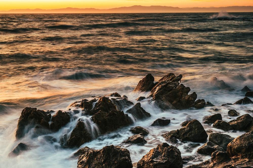 rock on beach under golden hour