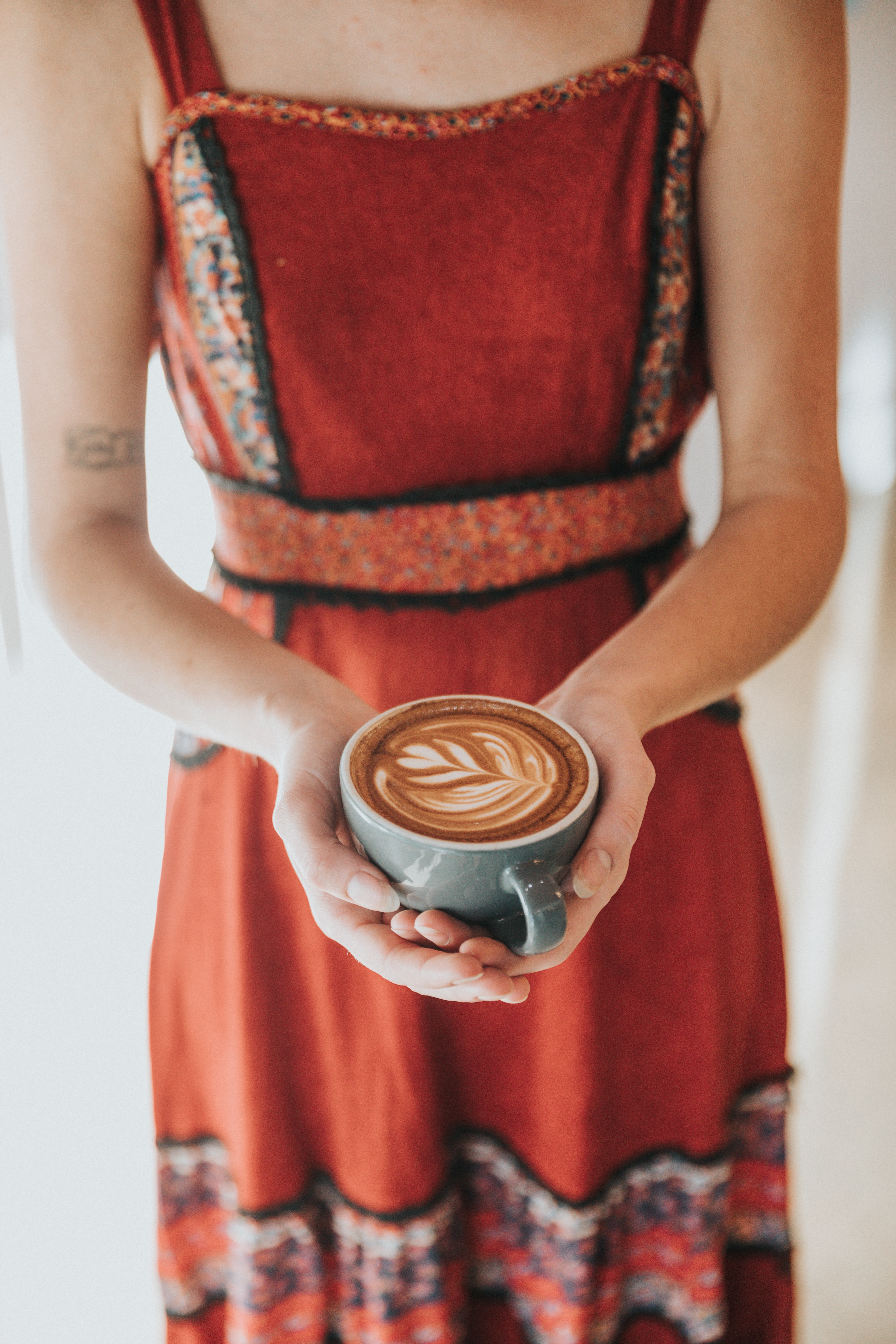 woman carrying coffee latte with art