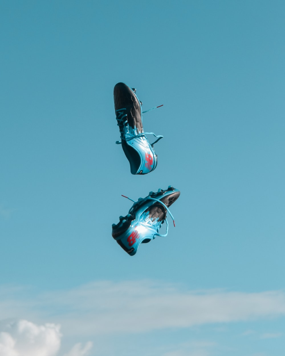 pair of blue-and-black New Balance cleats in the air under teal sky with white clouds