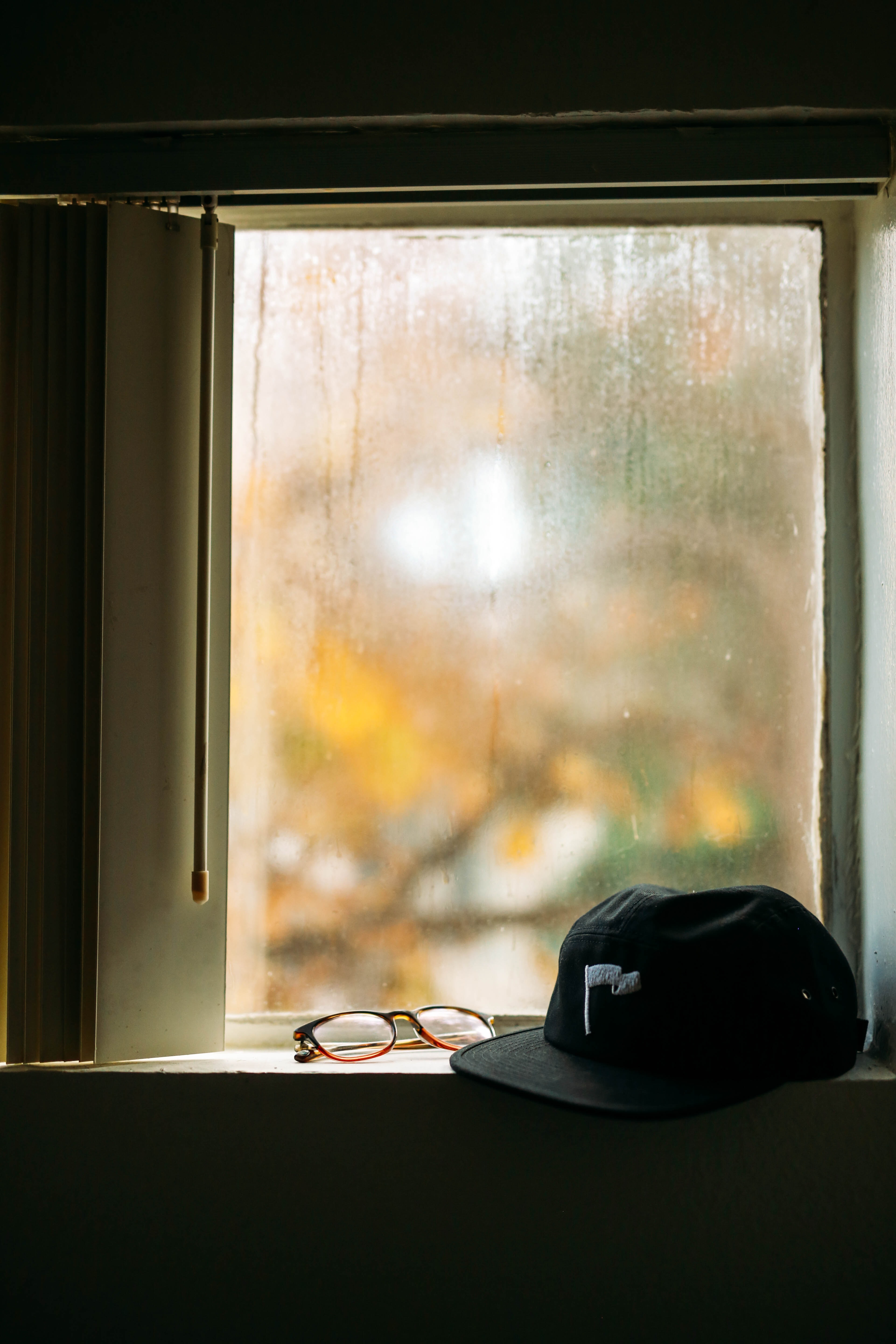 black cap and eyeglasses in front of window