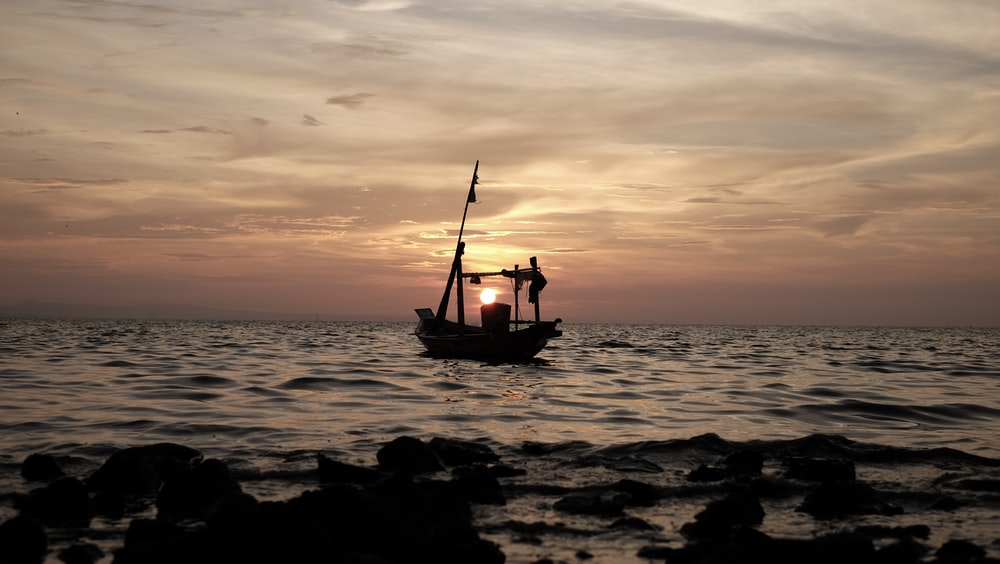 silhouette of boat on body of water with sunset