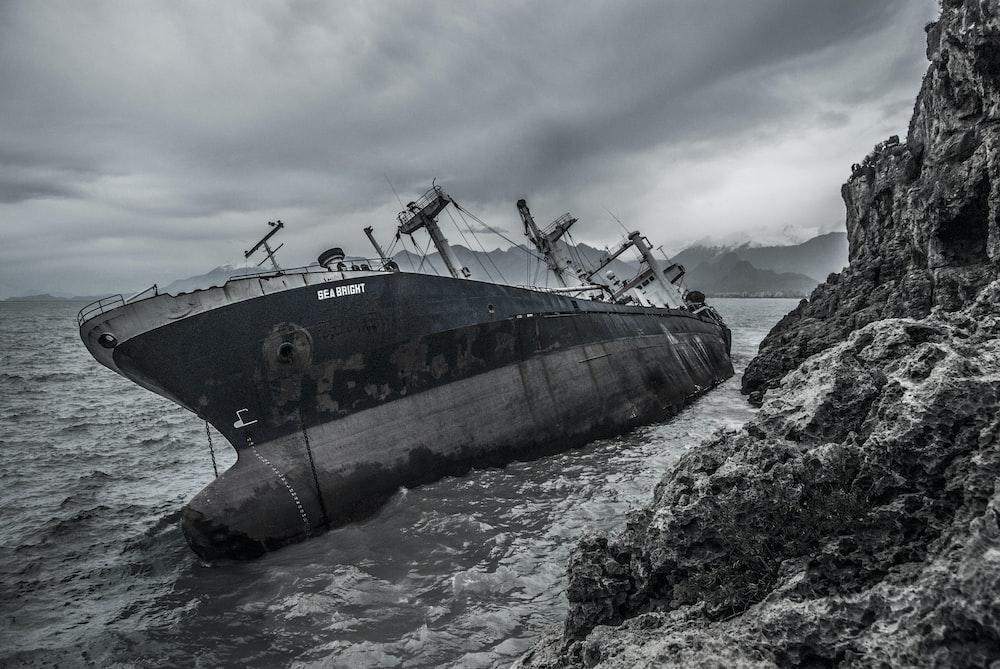 black military ship maneuvering beside stone mountain