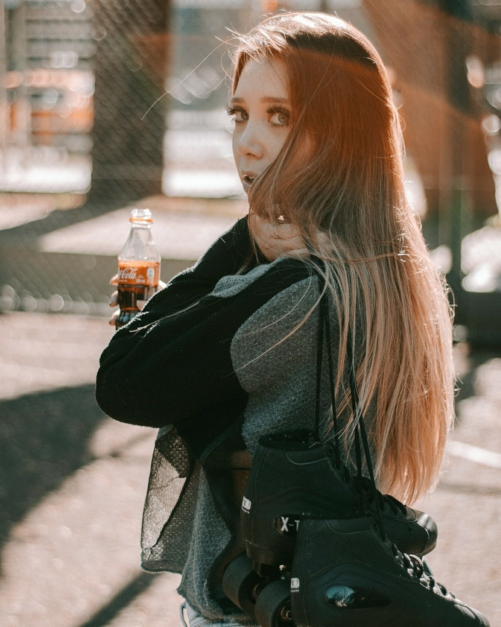woman wearing black and gray jacket holding bottle of coke