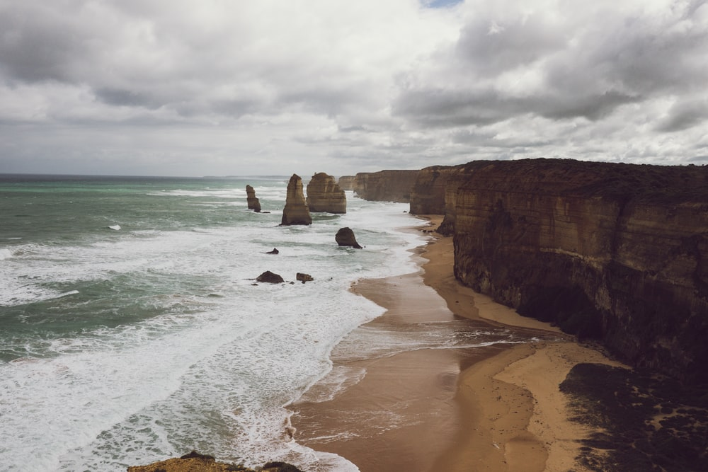 brown cliff near seashore in landscape photography