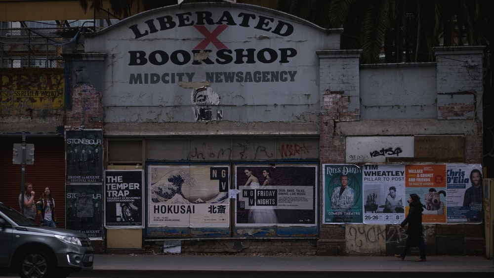 gray car in front of Liberated Bookshop sigange