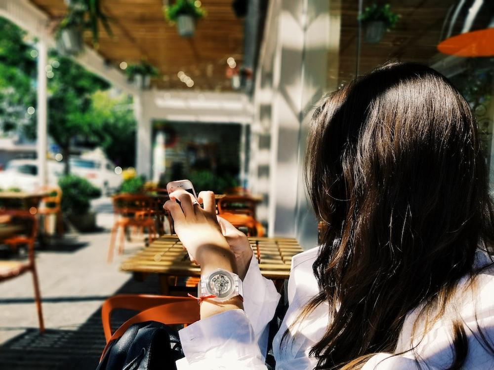 woman using phone near brown table