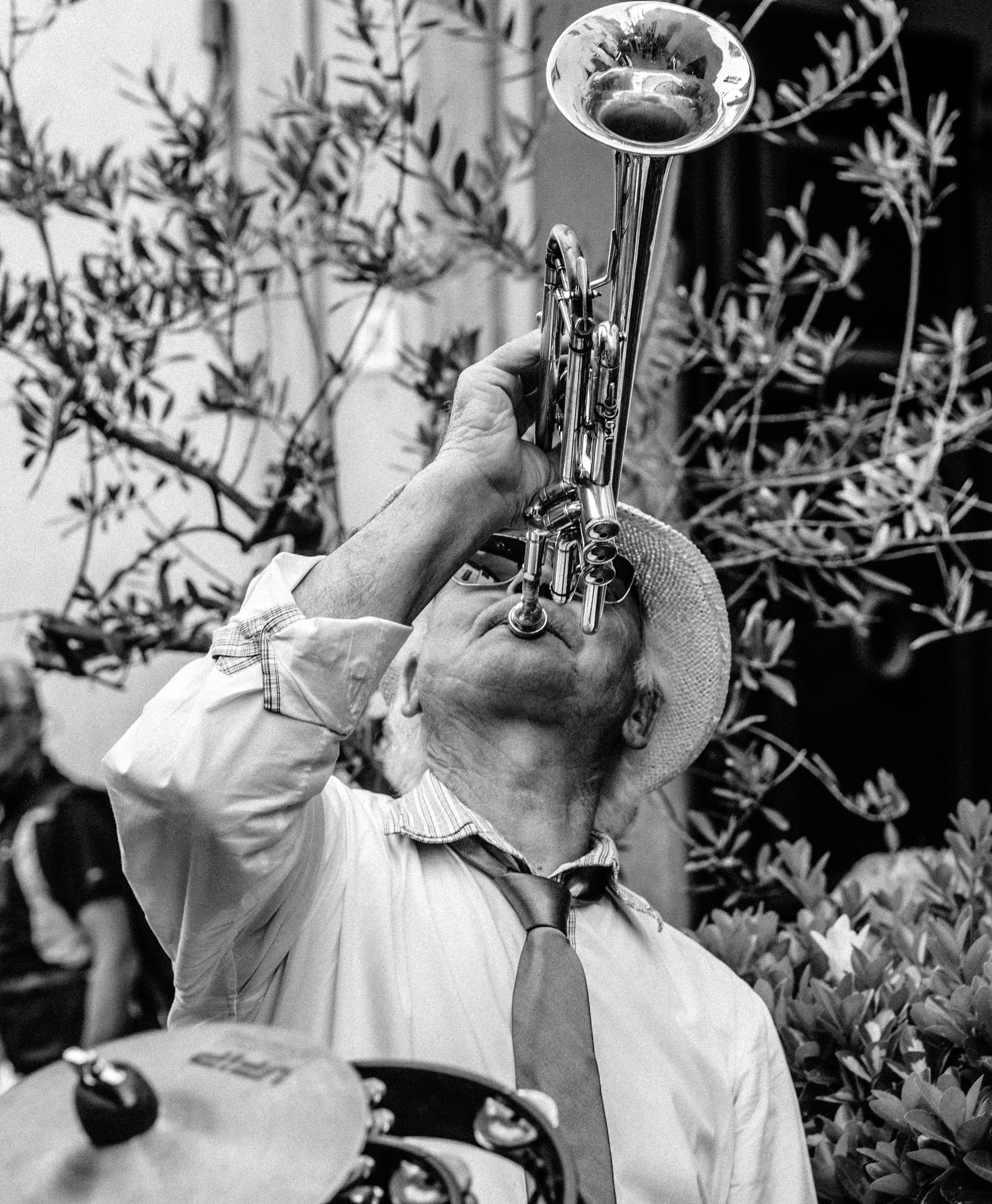 grayscale photography of man playing trumpet