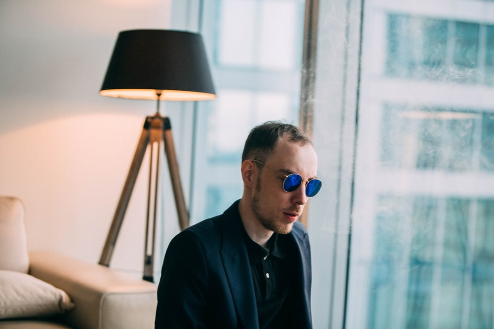 man wearing sunglasses near table lamp photo